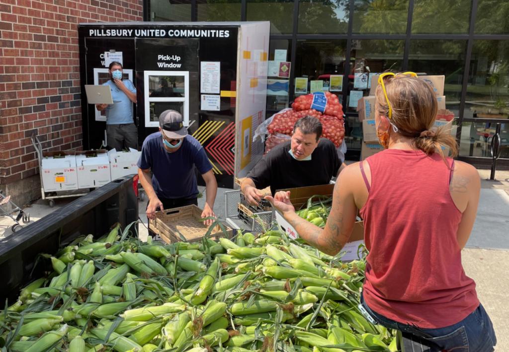 Pillsbury Food Bank staff help unload sweet corn.